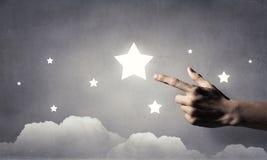 Atteignez et touchez l'étoile photographie stock