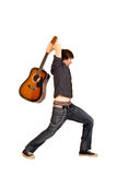 Attempting to destroy his instrument. Guitar player attempting to destroy his instrument , over white stock images