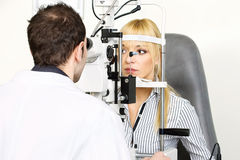 Attendance at the optometrist. Female patient is having a medical attendance at the optometrist Stock Images