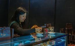 Attendant at chocolate festival prepares sample with toothpick. Seoul, South Korea, January, 19, 2018:          Attendant at chocolate festival prepares sample Royalty Free Stock Image