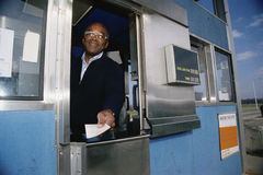 Attendant giving a ticket Royalty Free Stock Photography
