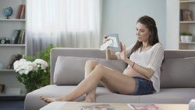 Attendant la dame sur le divan jetant le sonogram encadré et le coup d'oeil de lui, anticipation banque de vidéos