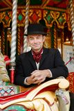 Attendant riding traditional carousel Royalty Free Stock Images