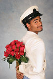 Attendant waiting with roses. Attendant waiting with bouquet of red roses in white jacket and hat Stock Photography
