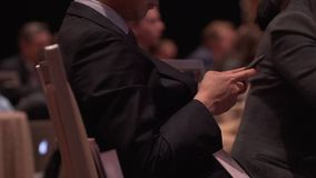 Attendee using phone at a conference stock video