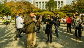 Attendees enjoy a variety of food while walking around. Daejeon, South Korea-November, 8,2017: Attendees at Woojeong Helpers Culture Festival at Woosong College Royalty Free Stock Image