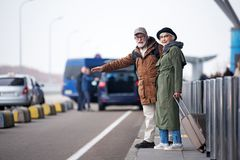 Senior couple is trying to stop car. Attending new town. Full length of optimistic old men and women are standing near road and trying to catch taxi. Gentleman Stock Photos