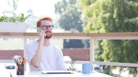 Attending Phone Call, Communicating, Sitting Outdoor Stock Photo