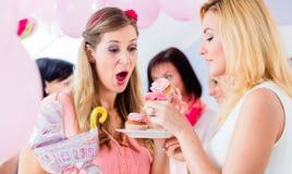 Attendre la mère mangeant le petit gâteau sur la partie de fête de naissance Image libre de droits