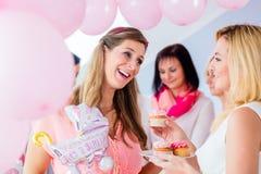 Attendre la mère mangeant le petit gâteau sur la partie de fête de naissance Photos stock