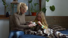 Caring mother giving her ill daughter hot tea stock video