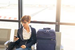 Attente dans le terminal d'aéroport utilisant le téléphone Photo libre de droits