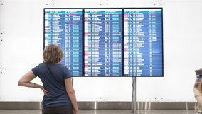 Attente de femme le départ dans l'aéroport, panneau de départ, affichage électronique d'horaire d'aéroport, statique ?lectronique banque de vidéos