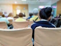 Attente de jeune femme et de beaucoup de personnes médicale et services de santé à l'hôpital, patients attendant le traitement à  image stock
