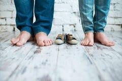 Attente de la chéri Chaussures du ` s d'enfants avec les pieds de parents Photographie stock