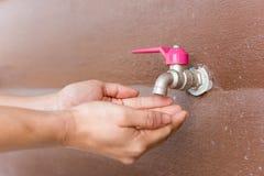 Attente de main l'eau du vieux robinet Photos stock