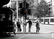 Attente de trois hommes pour traverser la rue de Flinders à Melbourne, Australie Photos stock