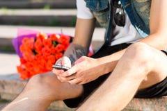 Attente de vous ! Message de dactylographie de jeune homme sur le wh de téléphone portable photo libre de droits