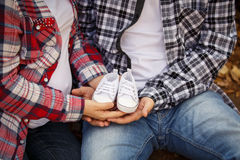 Attente du bébé garçon Petits petits chaussons blancs du ` s de bébé dans le ` s de maman et des mains du ` s du DA Images libres de droits