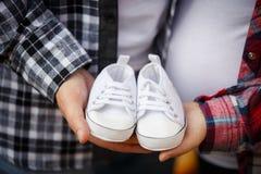 Attente du bébé garçon Petits petits chaussons blancs du ` s de bébé dans le ` s de maman et des mains du ` s du DA Image stock