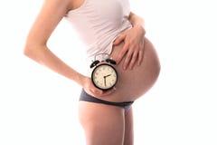 Attente du bébé, le ventre de femme enceinte avec l'horloge, whi Photographie stock libre de droits