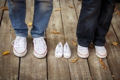Attente du bébé Les petits petits chaussons blancs du ` s de bébé s'approchent du ` s de maman et du ` s du DA Photographie stock libre de droits