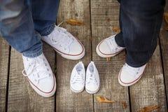 Attente du bébé Les petits petits chaussons blancs du ` s de bébé s'approchent du ` s de maman et du ` s du DA Image libre de droits