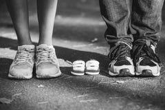 Attente du bébé Petits butins, espadrilles près des pieds de mon père et mère Femme enceinte, grossesse, maternité Image libre de droits
