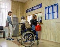 Attente handicapée dans la ligne à l'enregistrement d'établissement médical photo stock