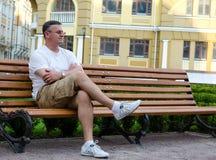 Attente se reposante d'homme sur un banc urbain photographie stock