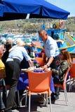 Attente sur des tables dans le port de Marsaxlokk Photos stock