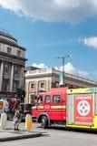 Attentes de piétonne de femme comme passages de camion de pompiers Photographie stock libre de droits
