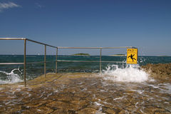 Attention. Wave crashing on the shore with attention sign Royalty Free Stock Photo