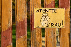Beware of the dog!. `Beware of the dog!` sign (in Romanian language) with dog drawing on the wooden fence royalty free stock image