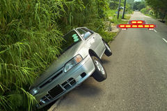 """Attention! Car accident. Car exceeded speed limit  and fall down in to the ditch. The red """"Alarm """"signal is behind of it Stock Image"""