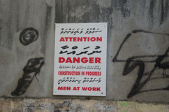 Attention danger construction in progress. Men at work sign on graffiti wall Stock Images