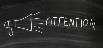 Attention. Dark blackboard with drawn megaphone and written words attention stock photo