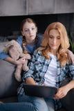 Attention de attente sombre de mère de petite fille à la maison photo libre de droits