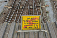 Attention high voltage sign train tracks in german language. Attention high voltage sign near train tracks in german language Royalty Free Stock Photo