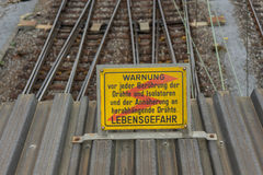 Attention high voltage sign train tracks in german language. Attention high voltage sign near train tracks in german language Royalty Free Stock Images