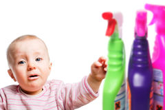 Attention: Infant wants to play with cleaner. Curious infant is approaching to some  cleaning agents Stock Photo