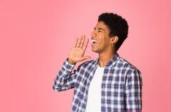 Attention ! Jeune type dans la main à carreaux de participation de chemise près de la bouche image stock