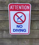 Attention No Diving Warning Sign. Red, white and blue sign written in all capital letters is pictured and says, Attention No Diving providing a warning sign at royalty free stock images