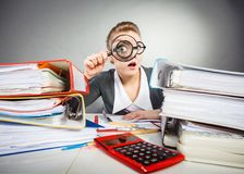 Crazy office lady at desk. Attention paperwork corporate details workaholism concept. Crazy office lady at desk. Workaholic secretary holding magnifying glass Stock Photography