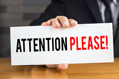 Attention please, message on white card and hold by businessman Stock Photography