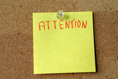 Attention. Yellow note with the word attention on it, pinned to a corkboard royalty free stock photos