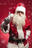 Attention! santa claus is warning all the bad kids. On red background Royalty Free Stock Photos