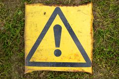 Attention sign. Old yellow attention sign on green grass stock photo