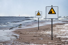 Attention signs near sea with stormy weather Royalty Free Stock Photo