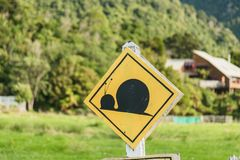 Attention snail. Danger yellow road sign. Slow driver Caution. New Zealand stock image